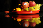 Bao-jhong Yi-min Temple, Kaohsiung -- Offering of fruits and tea appease the temple gods.<br /> <br /> Seen on this platter are bananas, apples and oranges, typical fruits offered to the gods at a Taiwanese temple.<br /> <br /> 'Apple' in Mandarin is 'ping guo', the first character of which sounds the same as the word 'peace' ('ping') in Chinese.<br /> <br /> &quot;Ju' in 'ju zi' for 'orange' sounds very similar to 'ji', the character for 'lucky' or 'auspicious' in Chinese.<br /> <br /> And finally, the second character in 'xiang jiao' for 'banana' - when pronounced in the local Taiwanese (Min-nan) dialect - sounds like the Chinese word for 'summon' or 'call', and thus represents summoning or calling one's good fortune.<br /> <br /> A cup of tea is offered to the gods as well to gain their favor.