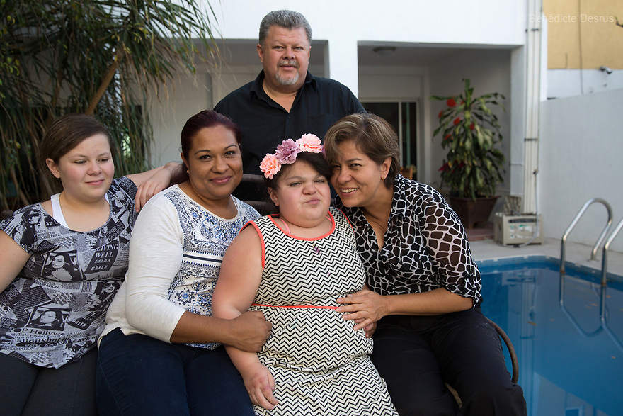 "Ana Ximena Navarro (C) and her family are pictured at their home in Guadalajara, Mexico on February 22, 2017. Ximena was diagnosed as an infant with Hurler syndrome. Hurler syndrome is the most severe form of mucopolysaccharidosis type 1 (MPS1), a rare lysosomal storage disease, characterized by skeletal abnormalities, cognitive impairment, heart disease, respiratory problems, enlarged liver and spleen, characteristic facies and reduced life expectancy. Ximena was being given enzyme replacement therapy (ERT) when she was 19 months old, and she was suddenly able to eat and sleep. She is now 12, and has normal hormonal development for her age, although some mental delay, according to her father. ""Without the treatment, she would have died from all the complications — untreated, children have a very bad quality of life and typically die before they are seven"", her father says. Photo credit: Bénédicte Desrus"