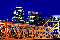 Minneapolis skyline and Irene Hixon Whitney Bridge in Minneapolis, Minnesota at night.  Designed by Twin Cities-based artist Siah Armajani.  The bridge was built in 1988.  It is made of steel, wood, paint, concrete, brass and is 379 feet in length.