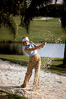 Attractive young golfer hitting out of the sand trap