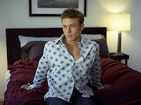handsome young man sitting on the edge of a bed