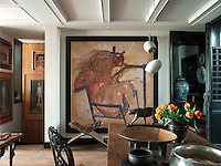 A dramatic painting dominates one wall of the dining area