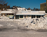Piled and plowed snow form new traffic control barriers and block store and restaurant access along Rehoboth Avenue in Rehoboth Beach, Delaware, USA, the morning after the blizzard of February 2010.