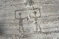 Petroglyph, rock carving, of two warriors with swords and small round shileds carved by the ancient Camuni people in the iron age between  900-1200 BC. Rock 26-27, Foppi di Nadro, Riserva Naturale Incisioni Rupestri di Ceto, Cimbergo e Paspardo, Capo di Ponti, Valcamonica (Val Camonica), Lombardy plain, Italy
