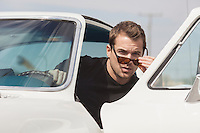man lowering his sunglasses while exiting a car