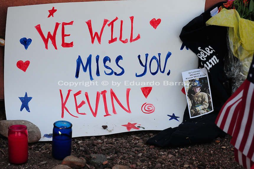 """Phoenix, Arizona. July 3, 2013. A small makeshift memorial for the 19 Arizona firefighters who died on June 30 battling the Yarnell Hill wildfire was built outside the Forensic Science Center in Phoenix, where autopsies are being conducted. """"We will miss you Kevin"""", reads this sign made to honor Kevin Woyjeck, 21, who is among the 19 victims of the Yarnell Hill wildfire in Arizona. Photo by Eduardo Barraza © 2013"""