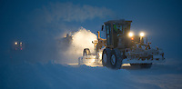 A Cruz Construction Inc. motor grader works behind an ejector truck dumping ice chips near the end of the 27 mile long Prudhoe Bay - Badami ice road on Januray 24, 2013. The road to Badami is part of a longer winter-only corridor to the Point Thompson field.