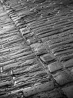 The cobbles of Gentle Street, Frome, Somerset in black and white.