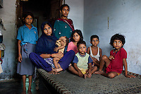 "Sitara (aged 35, 2nd from left), sits with her 7 children (5 daughters & 2 sons) as she breastfeeds her 8 month old baby girl in a village in Allahabad, Uttar Pradesh, India. ""I wish that I could stop getting pregnant but our religion says that children are a gift of God."" Sitara is an illiterate muslim lady whose husband works as a vegetable vendor in the local village market. They have resisted all advises of permanent sterilization from the local village-level health workers. Children from left to right : Roshni (10), Tamanna (8 months), Chandni (14), Sufia (8), Asif (3), Ajman (5), and Rani (7). Photo by Suzanne Lee / Panos London"