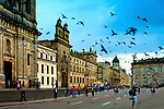 Piegons fly over Plaza de Bolivar in Bogota, Colombia.  The historic 17th century Capilla del Sagrario rises above the squares' lower buildings.