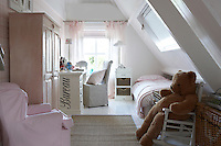 To make the most of the space in a girl's attic bedroom the bed is tucked under the skylight