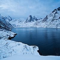 Mountain peaks rise above Djupfjord in winter, Moskenesoy, Lofoten Islands, Norway
