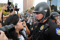 Phoenix, Arizona. April 25, 2012 - Phoenix Police officer L. Hunt and demonstrator Sandra Castro stare at each other. They came face to face as officers were slowly pushing protesters back toward the sidewalk. About 500 people protested the controversial law on the same day U.S. Supreme Court justices heard legal arguments on the Arizona vs. United States case. At the end of the march, six activists blocked Central Avenue by sitting in the middle of the street. They all were arrested by the Phoenix Police Department and taken to the Fourth Avenue County Jail. Photo by Eduardo Barraza © 2012