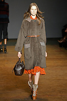 Kirsi Pyrhonen walks runway in a deep chocolate jet set alpaca coat, sedona red galena embroidery dress, espresso voyage drawstring bag, and tan platform shearling booties, from the Marc by Marc Jacobs Fall/Winter 2011 collection, during New York Fashion Week, Fall 2011.