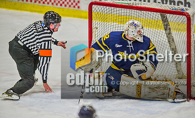 21 February 2015:  NCAA Referee Tom Fyrer spins to the ice as Merrimack College Warrior Goaltender Rasmus Tirronen, a Senior from Espoo, Finland keeps his eye on the play during the first period against the University of Vermont Catamounts at Gutterson Fieldhouse in Burlington, Vermont. The teams played to a scoreless tie as the Cats wrapped up their Hockey East regular home season. Mandatory Credit: Ed Wolfstein Photo *** RAW (NEF) Image File Available ***