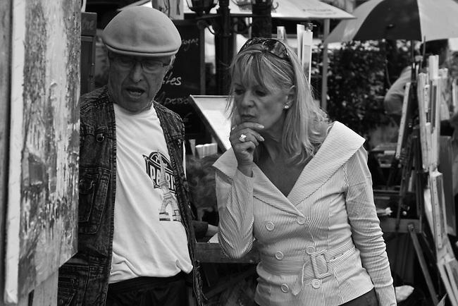 Sidewalk artist and client. Montmartre district, Paris, France. July 29, 2007.