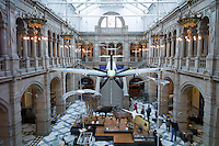 Visitors at Kelvingrove Art Gallery and Museum with suspended Spitfire World War II airplane exhibit on display in the West Court in Glasgow, Scotland