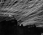"Japanese night raiders are greeted with a lacework of anti-aircraft fire by Marine defenders at the Yontan airfield on Okinawa. Silhouetted against the paths of tracer bullets are Marine Corsair fighter plans of the ""Hell's Belles"" squadron. Photograph by Michael J. Lesko, Sr."