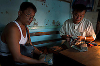Jade traders count their money at the Jade Market in Mandalay. Much of the Burmese junta's wealth comes from the trade in precious stones.