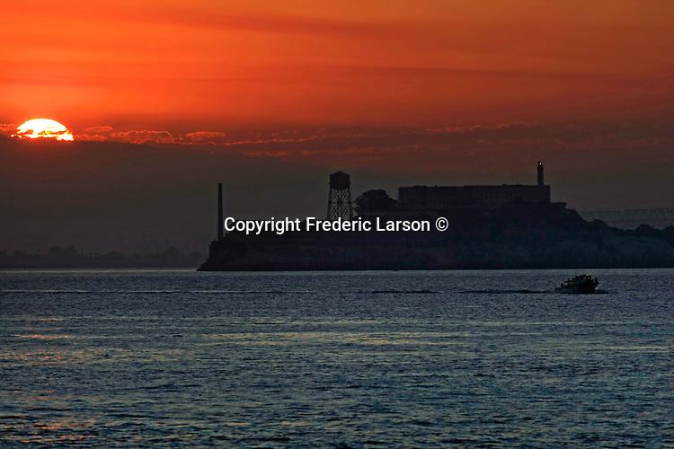 The sunrises over Alcatraz Island as fisherman head out to sea in a small boat.