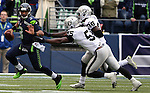 Seattle Seahawks quarterback Russell Wilson (3) scrambles away from Oakland Raiders  linebacker Sio Moore  (55) and cornerback T.J. Carrie (38) during the third quarter  at CenturyLink Field in Seattle, Washington on November 2, 2014. Wilson rushed for 31 yards and passed for 179 yards in the Seahawks 30-24 win over the Raiders.    The Seahawks beat the Raiders 30-24 in Seattle. ©2014. Jim Bryant Photo. All rights Reserved.
