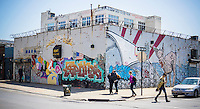 """Murals grace the walls in the so-called """"Five Points of Bushwick"""" in the Bushwick neighborhood of Brooklyn in New York on Saturday, April 27, 2013.  The owners of the buildings has allowed graffiti and street artists to decorate the blank walls of the industrial buildings. The neighborhood is undergoing gentrification changing from a rough and tumble mix of Hispanic and industrial to a haven for hipsters, forcing many of the long-time residents out because of rising rents.. (©Richard B. Levine)"""