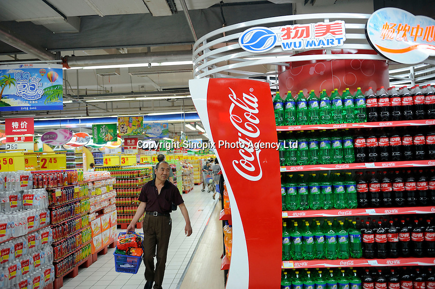 Customer shops in beverage section in Wu Mart supermarket in Beijing, China. Wu Mart, the Beijing-based chain, was founded in the early 1990s by Zhang Wenzhong. Its name smacks of the fame of U.S. retail giant Wal-Mart. Wu Mart and Wal-Mart are competing in different arenas and each appears to be going after a different class of consumer. By 2005, Wu Mart had more than 450 hypermarkets, supermarkets and convenience stores, and is one of only a few Chinese retailers whose shares are publicly traded. .02 June 2011.
