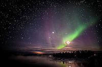 Star filled sky and moon with multicolored nothern lights ovrer water. (Photo by Travel Photographer Matt Considine)