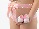 Pregnant woman with a pink bow on her belly holding baby shoes in her hand