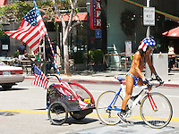 American Dan, always the patriot, rides his bicycle along Broadway Ave with the American flag in tow on Saturday, July 28, 2012.