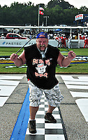 World's Strongest Redneck (Steve McGranahan) bends steel bar over his head at the start of the 2009 NASCAR Truck race Memphis Motorsports Park