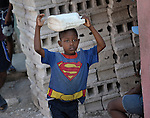 A boy carries water on his head as he walks along a street in Port-au-Prince, Haiti.
