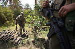 Marine combat engineers and Navy explosive ordinance disposal personnel uncover and destroy a cache of more than 160 heavy 120mm mortars and other weaponry after a sweep by Kilo Co. 3rd Battalion 1st Marines (3/1) and attached units through palm groves along the Euphrates River in Hit, Iraq on Sunday September 25, 2005.