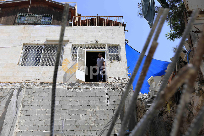 A members of the Palestinian Abu Sbina family looks on the rubble of his home after it was demolished by Jerusalem municipality workers in the mostly Arab Jerusalem neighbourhood of al-Thawri on April 30, 2013. Palestinian homes built without an Israeli construction permit are often demolished by order of the Jerusalem municipality. Photo by Sliman Khader