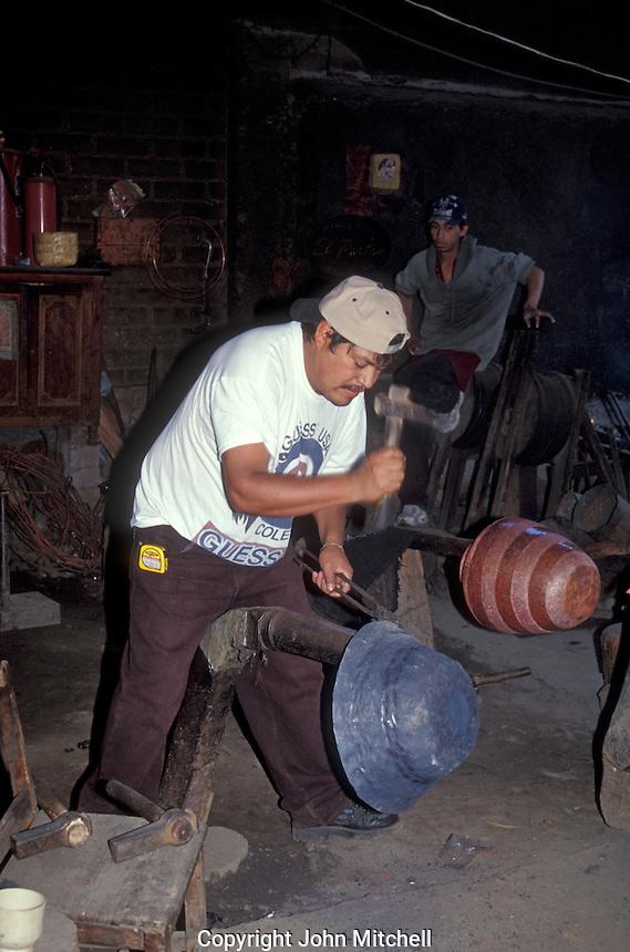 Coppersmith hammering a pot in a workshop  the village of Santa Clara del Cobre near Lake Patzcuaro, Michoacan, Mexico