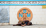 A sick, homeless woman lies on the street outside the walls of the Notre Dame Cathedral in Cotonou, Benin.