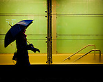 A blurred woman with an umbrella walking in the rain.