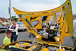 Bellmore, New York, USA. 12th June 2015. A family looks at a modified yellow 2003 Corvette 50th Anniversary model, with Lamborghini doors (AKA vertical scissors doors and Lambo doors) whose passenger door glass can be seen at left, and chrome trim added to inside of hood to reflect engine, an award winning car owned by Grey Cherveny of Bay Shore, is displayed  at the Friday Night Car Show held at the Bellmore Long Island Railroad Station Parking Lot. Hundreds of classic, antique, and custom cars were on view at the free weekly show, sponsored by the Chamber of Commerce of the Bellmores.