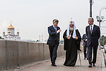 An aide, left, talks with Kirill I, patriarch of the Russian Orthodox Church, and Moscow Mayor Sergei S. Sobyanin, right, during a campaign appearance on a sidewalk between the Kremlin walls and the Moscow River on Thursday, August 29, 2013 in Moscow, Russia.
