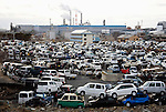 Trashed vehicles await transportation to demolition sites while a factory returns to business in Ishinomki, Miyagi Prefecture, Japan on  07 Mar. 2012. While residential and business areas have been cleared of rubble from the March 11 2011 tsunami, debris remains in huge mounds due to a lack of will by many parts of the country to accept it for fearit may be contaminated with radioactivity from the Fukushima Daiichi nuclear power plant..Photographer: Robert Gilhooly