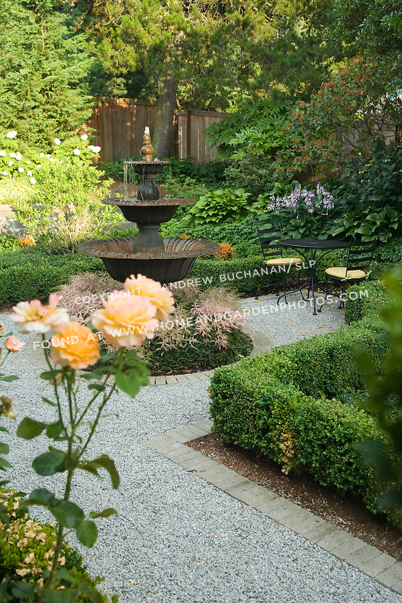 a formal backyard garden, edged with roses, framed by boxwood, and paved with gravel around a central water feature surrounded by astilbe, sits in the quiet late afternoon light behind a home in a suburban community east of Seattle; patrick