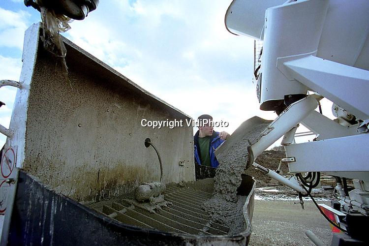 Foto: VidiPhoto..ZEVENAAR - Een onafgebroken stroom van beton wordt vrijdag in de tunnelbak voor de Betuwelijn bij Zevenaar gegoten. De enorme klus duurde van 's morgens vroeg tot diep in de nacht. In totaal werd er 1500 kubieke meter beton gestort. Dat gebeurde door in totaal 22 vrachtwagens die op en neer reden naar Kalkar om het materiaal te halen. Bij de werkzaamheden werd gebruik gemaakt van duikers, om te voorkomen dat er obstakels in het beton terecht kwamen. De tunnelbak bij Zevenaar wordt 2 kilometer lang.