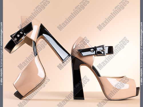 Fashion still life of a pair of sexy womens open-toe high heel platform shoes isolated on beige background