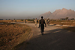 An Afghan police officer follows behind U.S. soldiers from  Company D, 1st Battalion, 22nd Infantry Regiment during an early morning patrol in Malajat, near Kandahar, Afghanistan. Oct. 9, 2010. DREW BROWN/STARS AND STRIPES