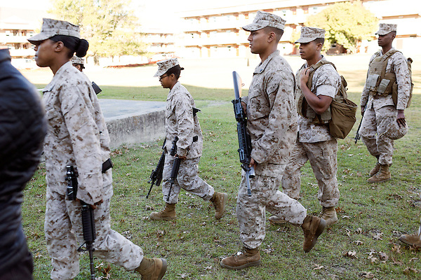 October 22, 2014. Camp LeJeune, North Carolina.<br />  LCpl. Jada Connor, center, carries rifles to the training ground for a patrol simulation. Marines in 3rd Platoon of the Ground Combat Element Integrated Task Force are all considered provisional infantrymen as they have not been to the School of Infantry (SOI) previous to volunteering for the GCEITF.<br />  The Ground Combat Element Integrated Task Force is a battalion level unit created in an effort to assess Marines in a series of physical and medical tests to establish baseline standards as the Corps analyze the best way to possibly integrate female Marines into combat arms occupational specialities, such as infantry personnel, for which they were previously not eligible. The unit will be comprised of approx. 650 Marines in total, with about 400 of those being volunteers, both male and female. <br />  Jeremy M. Lange for the Wall Street Journal<br /> COED