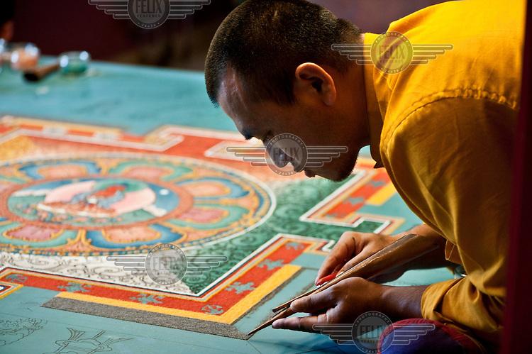 A monk draws a Mandala in Dashan Kagyu Ling Buddhist temple in Burgundy.