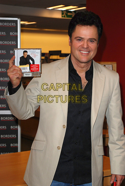 DONNY OSMOND.Signs copies of his new album in Borders Book Shop, Oxford Street, London, England, 9th March 2007..half length black shirt beige jacket holding CD.CAP/CAN.©Can Nguyen/Capital Pictures