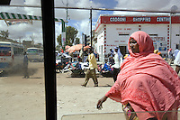 Somaliland. Waqohi Galbed province. Hargeisa town center. View from a car window on the street life. Market stall and shopping centre. A black muslim woman, wearing a pink veil on the head, and a group of men walk on the road. Smoky buses and dust. Somaliland is an unrecognized de facto sovereign state located in the Horn of Africa. Hargeisa is the capital of Somaliland. © 2006 Didier Ruef