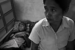 A woman watches over her son who is recovering from Malaria at the Mae Tao Clinic in Mae Sot. .The Mae Tao Clinic (MTC), founded and directed by Dr. Cynthia Maung, provides free health care for refugees, migrant workers, and other individuals who cross the border from Burma to Thailand in search of of medical treatment.
