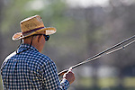 Man with a straw hat and sunglasses, fishing in Hermann Park, Houston, Texas.